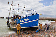 A fishing boat arriving back onto the beach  at Hastings, West Sussex. The fishermen drag the boat up the beach using a winch and guide it on wooden beams.
