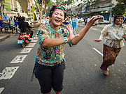 30 OCTOBER 2014 - BANGKOK, THAILAND:  A woman dances on Chakkaphatdi Phong Street during the parade marking the start of the annual temple fair at Wat Saket. Wat Saket is on a man-made hill in the historic section of Bangkok. The temple has golden spire that is 260 feet high which was the highest point in Bangkok for more than 100 years. The temple construction began in the 1800s in the reign of King Rama III and was completed in the reign of King Rama IV. The annual temple fair is held on the 12th lunar month, for nine days around the November full moon. During the fair a red cloth (reminiscent of a monk's robe) is placed around the Golden Mount while the temple grounds hosts Thai traditional theatre, food stalls and traditional shows.  PHOTO BY JACK KURTZ