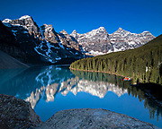 Scenic panoramic view of a blue sky over the turquoise waters of Lake Louise and the snow dusted Fairview Mountain in Banff National Park in Alberta, Canada.
