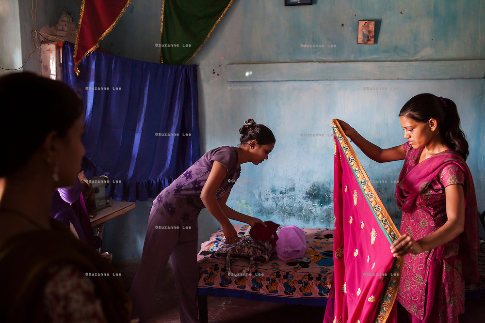 Video Volunteer videojournalist Niru J. Rathod's sister Mukta (center), 22, attends to her tailoring customers at home in Surendranagar, Gujarat, India on 14 December 2012. While Niru's sisters have become seamstresses or housewives, Niru, the 8th child in a family of 11 girls born to a Dalit construction worker, has been using videography for social change since 2006. She shoots and produces her own short documentaries and is a committed video activist, having conducted hundreds of village video screenings where she also speaks to thousands of men, shattering their ideas about what a woman and a Dalit can do while bringing massive changes to the communities she documents. Photo by Suzanne Lee / Marie Claire France
