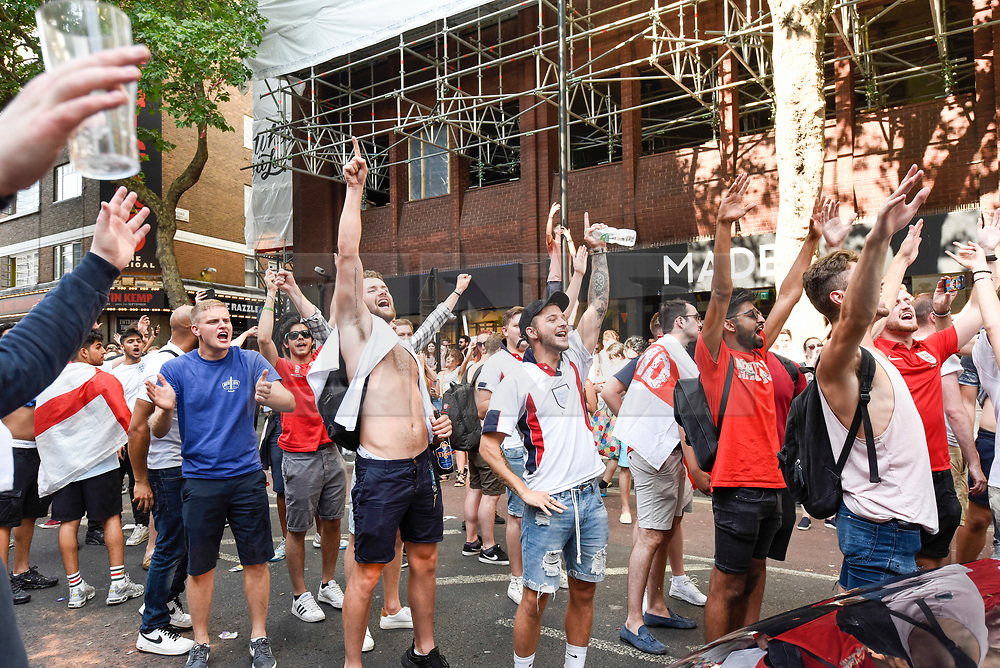 """© Licensed to London News Pictures. 07/07/2018. LONDON, UK. England fans in the capital celebrate the England national team's 2-0 victory against Sweden in the quarter-final match of the World Cup in Russia.  Jubilant fans in Charing Cross Road stop passing traffic chanting """"Football's Coming Home"""".  The annual Pride London event is also taking place in the area with happy rainbow clad Pride participants keen to celebrate as well.  England will face the winner of home team Russia or Croatia in the semi-final.  <br />   Photo credit: Stephen Chung/LNP"""