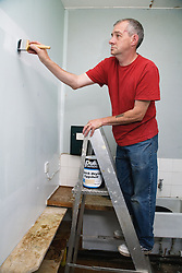 Painter and decorator painting wall in school science lab,