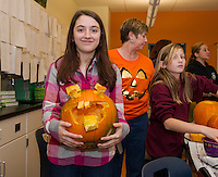 """Emma shows off her """"hillbilly"""" pumpkins she carved along with 7th grade students at Laconia Middle School on Wednesday morning.  (Karen Bobotas/for the Laconia Daily Sun)"""