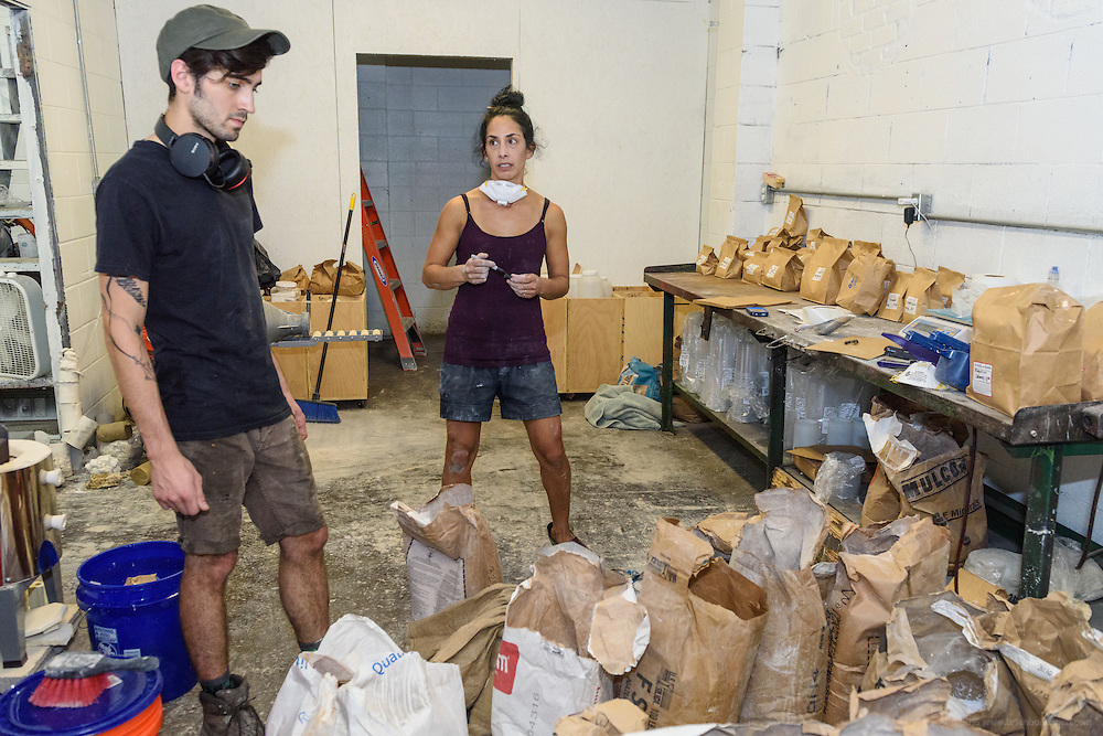 Lisa Simon talks with Luke Gnadinger, left, creative director at Kentucky Mudworks at 506 Baxter Avenue, as she fills an order for raw materials. Simon, a laid-off teacher at Jefferson Community and Technical College, now has a residency at Mudworks where she works about 12 hours a week and makes art in the studio space provided there. (Photo by Brian Bohannon)