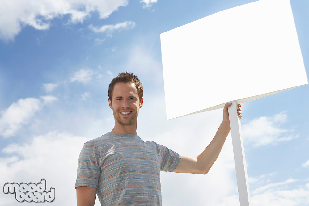 Portrait of man with standing by blank sign against cloudy sky