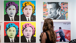 © Licensed to London News Pictures. 06/10/2016. London, UK. A woman views works by the street artist Cartrain depicting Kim Jong-un at the preview of Moniker Art Fair, part of London Art Week, taking place at the Old Truman Brewery, near Brick Lane.  Now in its seventh year, the fair embraces contemporary art from emerging and established artists, the majority of whom attend the fair in person in order to meet potential collectors and to show their work. Photo credit : Stephen Chung/LNP