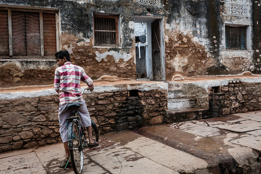 A boy rides his bike and waits for a friend in one of the streets of Bundi.
