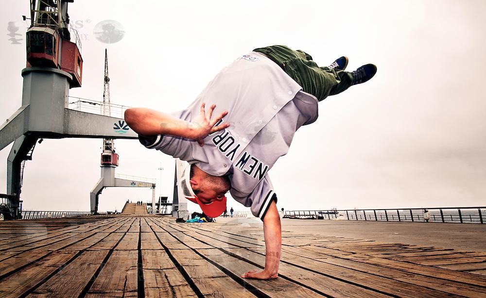 Breakdancer en el momento de saltar, apoyándose en el suelo. Sesión en el muelle Barón, Valparaíso, Chile.