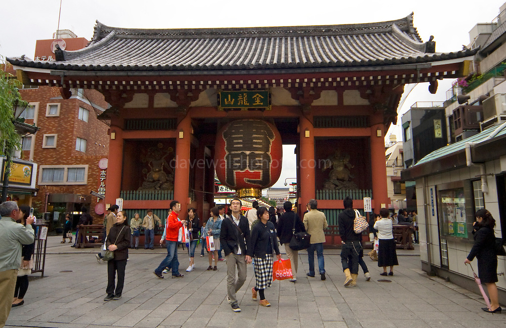 Tourists pass the giant lantern of the Kaminarimon or Thunder Gate, Asakusa, Tokyo. It's an entrance gate to the Senso-jo buddhist temple, popular with tourists and pilgrims...