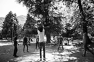 Migrants playing volleyball in the park close to their tents