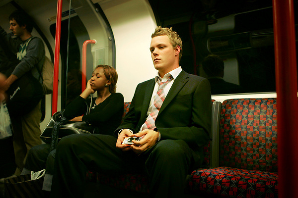 young man on the tube holding phone. 11/08/05 by Neville Elder