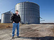 Rick Elliott stands in front of a 200,000 bushel grain bin on his farm in Monmouth, Illinois on Friday, February 17, 2012.