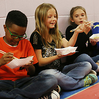 Saltillo Elementary School fourth grader Shelby Huggins smiles after use chopsticks to eat hibachi chicken and rice with her classmates Zavion Johnson, left, and Tylee Bowland, right, during their Japanese culture day at the culmination of their unit on the country and it's culture.