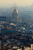 Looking down over Paris, France from the top of the Eiffel Tower. The golden dome of Invalides towers above the surrounding buildings.