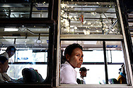 A woman gazes from a bus window on the streets of Yangon, Myanmar.