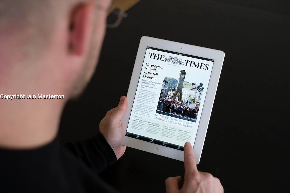 Man reading online mobile version of The Times newspaper on iPad3 tablet computer