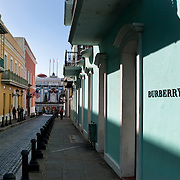 Scenic Old San Juan, Puerto Rico, originally founded in 1508 by the Spanish explorer Juan Ponce de León, is today a thriving carribean outpost of the United States.  The brightly-painted facades of the historic buildings often front trendy shops, including luxury clothing retailer Burberry.