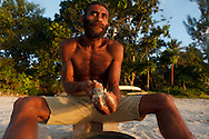 Ni Vanuatu Man making kava the traditional way - by grinding it with a piece of coral. Rah Lava Island, Torba Province, Vanuatu
