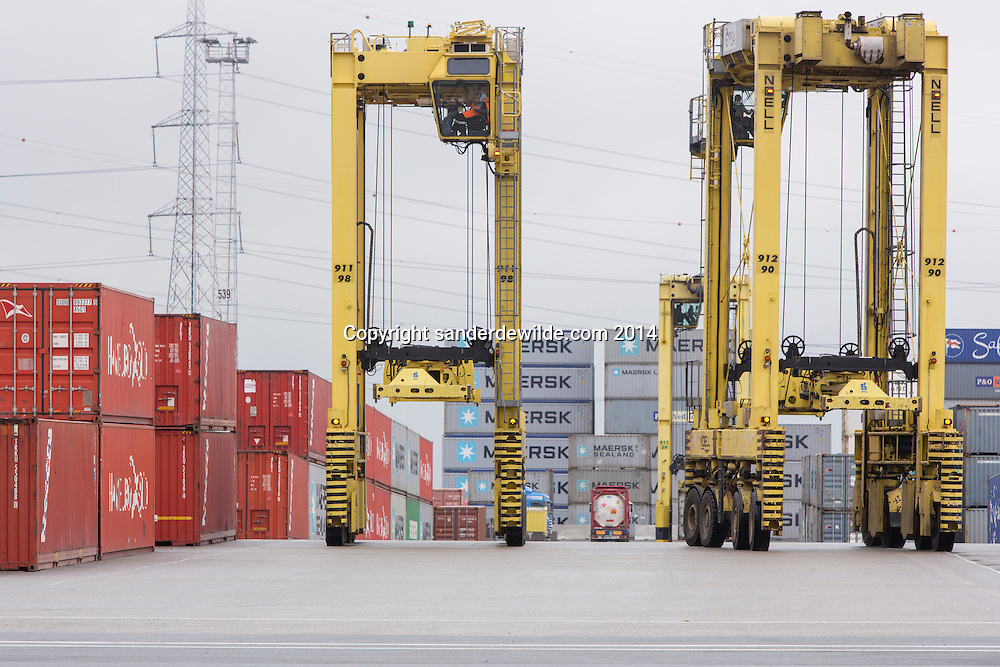 Yellow Noell straddle carriers with drivers in the top at Antwerp Gateway Deurganckdok. Deurganckdok is set to give more and larger container ships access to the Port of Antwerp