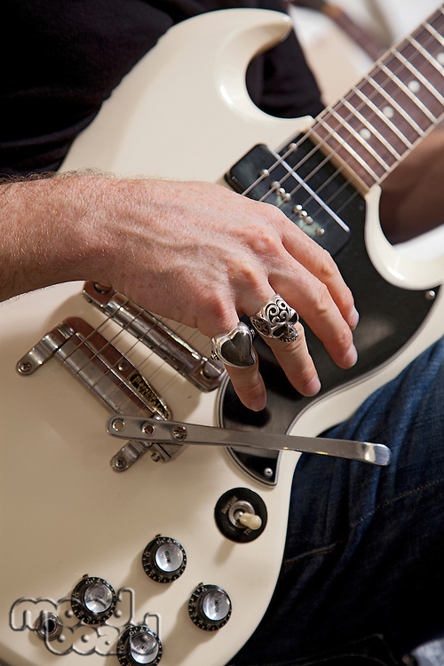 Close-up of man's hand playing electric guitar