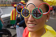 Wearing Olympic ring glasses, a lady sports fan tours central London during a break watching events during the London 2012 Olympics. Wearing their country's national colours the friends enjoy a respite from the summer rains to walk through the capital's streets.
