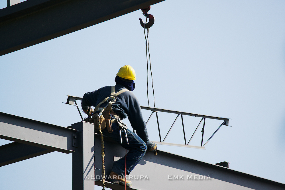 Ironworker recieves a piece of the steel framework delivered by crane.