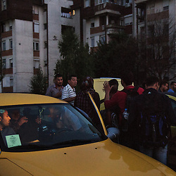 Refugees negotiate prices with taxis drivers in Gevgelija, Macedonia on August 26, 2015. After crossing the border into Macedonia, refugees make their way to the northern border with Serbia by train, bus or taxi. The approximately 2-hour taxi ride costs 100 euro.