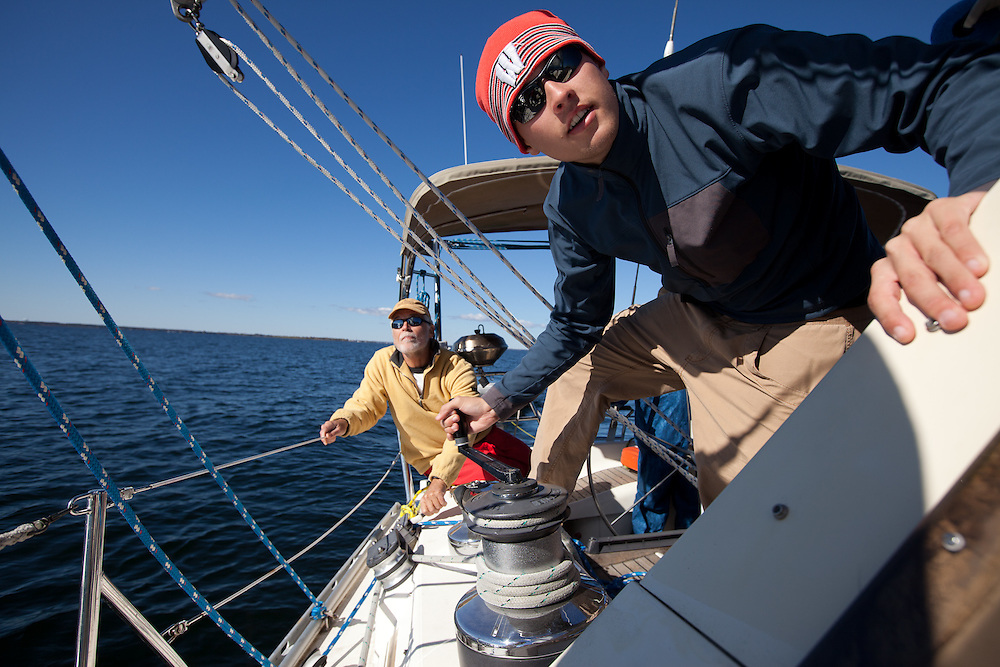 Young crew on a sailboat trims the headsail while the skipper looks on.