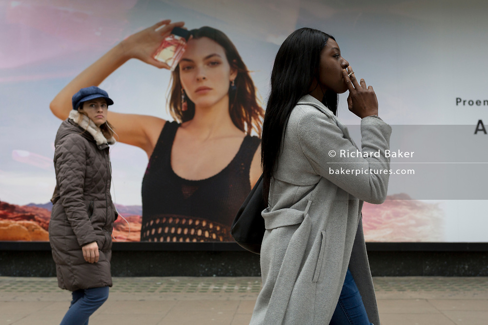 A woman smokes a cigarette while walking past a billboard ad featuring the face of a model advertising a perfume outside the retailer Debenhams on Oxford Street, on 16th April 2018, in London, England.