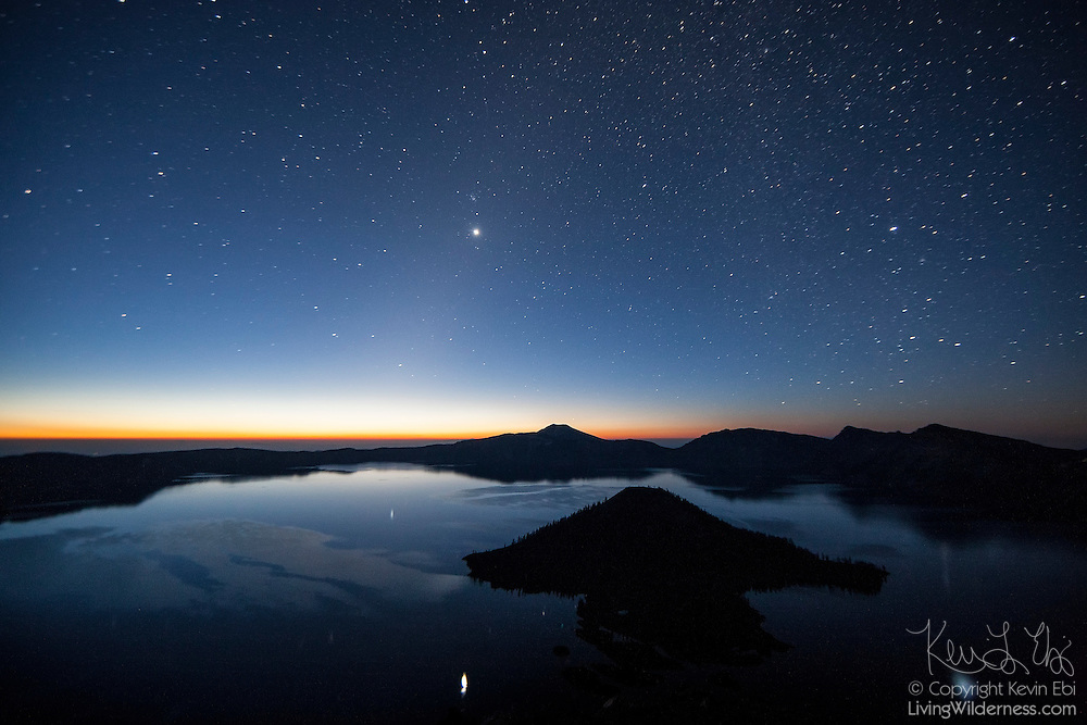 Thousands of stars and the planet Venus shine over Crater Lake in Oregon just before sunrise. The planet Venus is the brightest object in the sky and is visible near the center of the image and reflected in the lake. Crater Lake, which is actually a caldera, formed when Mount Mazama erupted violently about 7,700 years ago, causing its summit to collapse. Subsequent eruptions sealed the caldera, trapping rain water and snowmelt, forming the lake, which has a maximum depth of 1,949 feet (594 meters). Wizard Island, a volcanic cinder code, is visible in the foreground.
