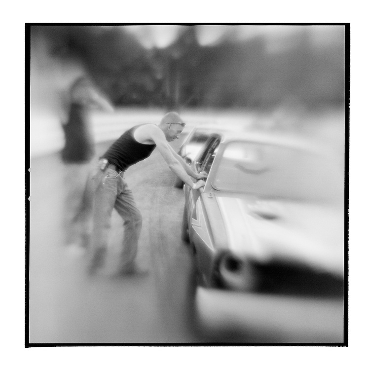 USA, Maryland, Mechanicsville, Blurred black and white image of man leaning against car during Demolition Derby at Potomac Speedway