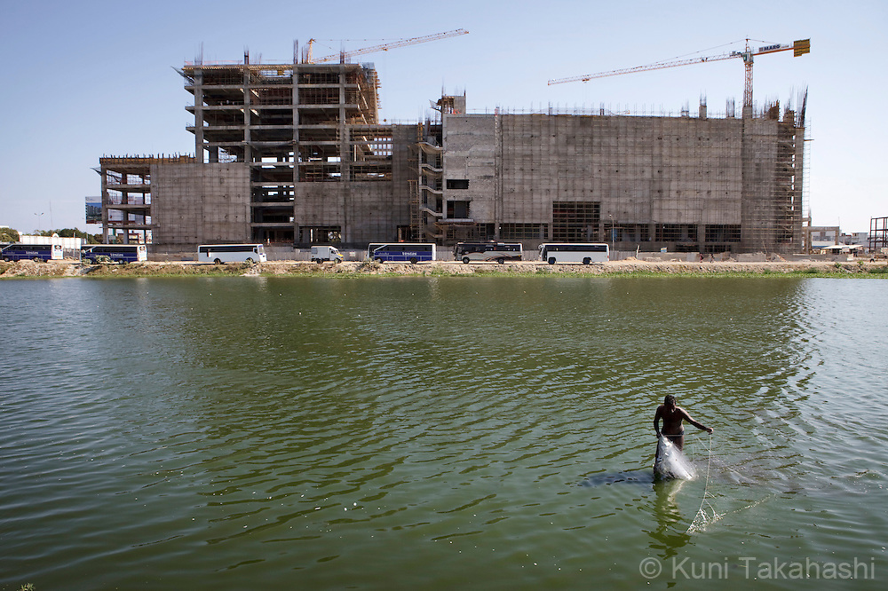 A man fishes in the river in front of construction of MARG Junction shopping mall in Chennai, India on April 16, 2012.<br /> (Photo by Kuni Takahashi)