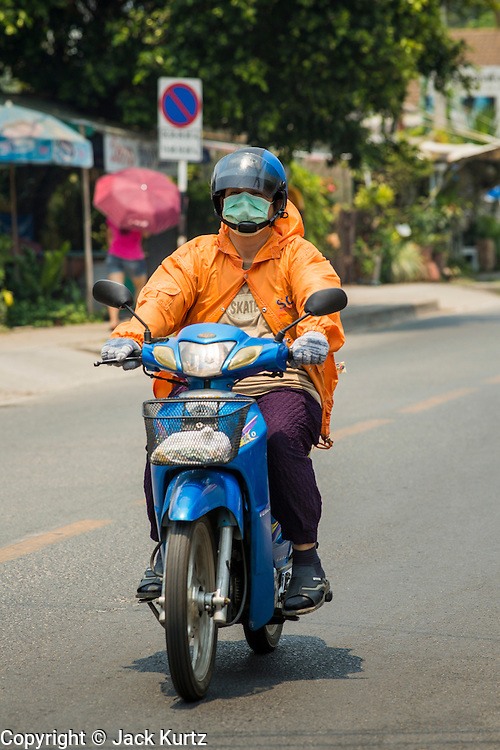 "08 CHIANG MAI, CHIANG MAI, THAILAND:    A woman wears a breathing mask while she drives her motorcycle through Chiang Mai, Thailand. Many people in Chiang Mai and nothern Thailand wearing masks because of the air pollution caused by smoke from fires in the area. The ""burning season,"" which roughly goes from late February to late April, is when farmers in northern Thailand burn the dead grass and last year's stubble out of their fields. The burning creates clouds of smoke that causes breathing problems, reduces visibility and contributes to global warming. The Thai government has banned the burning and is making an effort to control it, but the farmers think it replenishes their soil (they use the ash as fertilizer) and it's cheaper than ploughing the weeds under.   PHOTO BY JACK KURTZ"