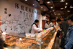 People buying snack food at open-air store, main street of Ciqikou Old Town, Chongqing, China.