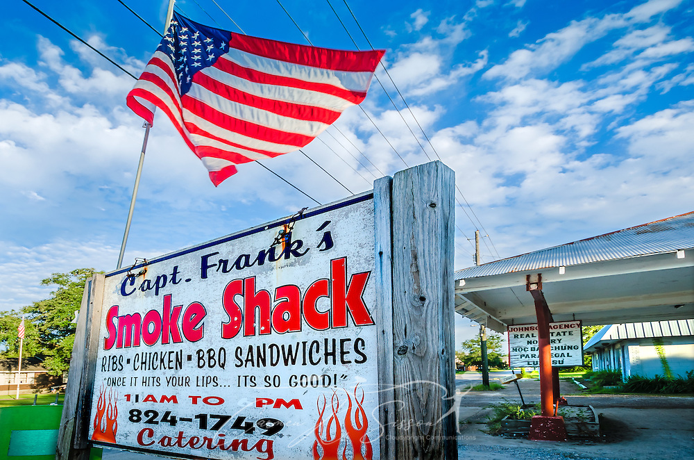 An American flag flies above Capt. Frank's Smoke Shack, Aug. 15, 2015, in Bayou La Batre, Alabama. Owner Frank Morse, a former merchant mariner and fishing captain, opened the barbecue shack in 2006 after Hurricane Katrina put him out of work. (Photo by Carmen K. Sisson/Cloudybright)