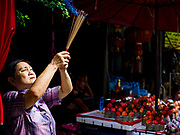 """05 SEPTEMBER 2017 - BANGKOK, THAILAND: A woman prays in Bangkok's Chinatown district on Hungry Ghost Day. The Ghost Festival is a Buddhist and Taoist holy day celebrated on the 15th day of the 7th lunar month. It is primarily celebrated in China and Chinese communities outisde China. In Thailand, it's celebrated in Thai-Chinese communities in Bangkok, Phuket and Chiang Mai.  On that day ghosts and spirits, including those of the deceased ancestors, come out from the lower realm to visit the living. Families prepare elaborate banquets for the spirits and burn """"ghost money"""" for the spirits to use in the other realm. It is a day for venerating dead relatives.      PHOTO BY JACK KURTZ"""