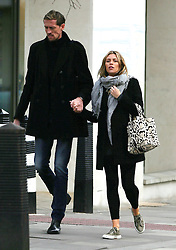 Abbey Clancy and footballer husband Peter Crouch out and about in London. The pregnant model looked happy and glowing wearing a black coat, grey top, scarf, black leggings and trainers... UK. 11/03/2015<br />