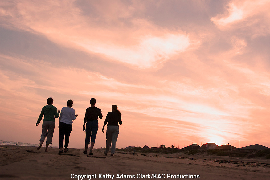 four women walking on beach at sunset, Galveston, Texas.  Silhouette.