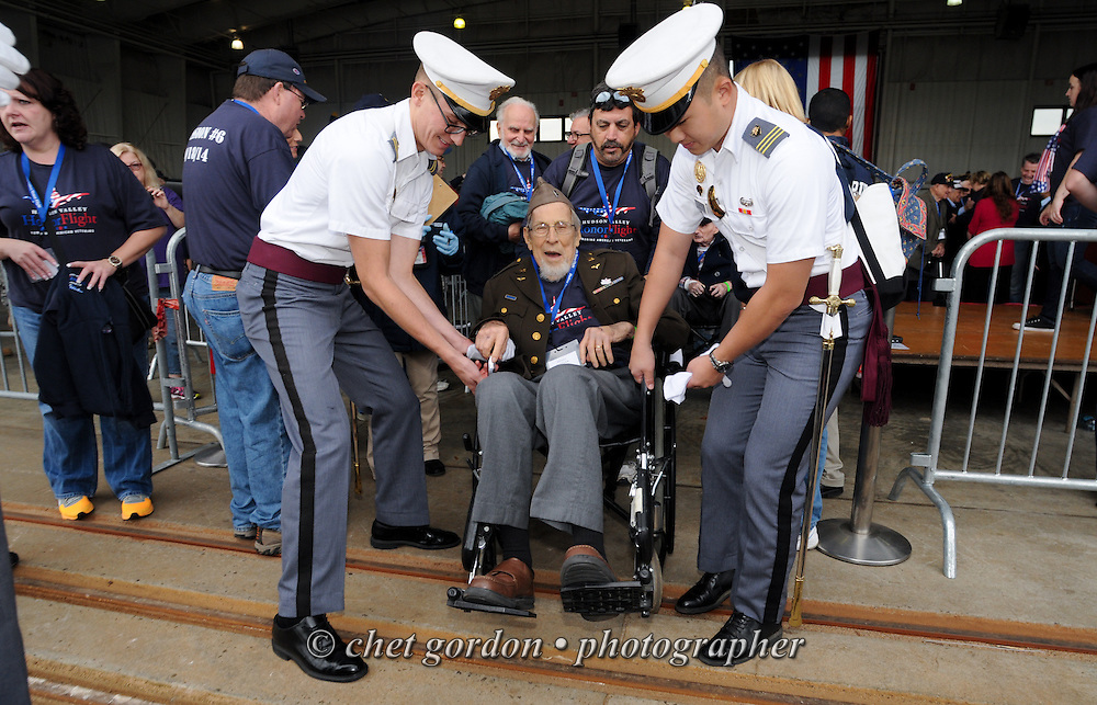 Two West Point cadets escort WWII Veteran Henry Sandler (center) to a waiting bus after a sendoff ceremony at Westchester County Airport in White Plains, NY on Saturday, October 18, 2014. Seventy-five WWII Veterans from the Westchester County area toured the WWII Memorial and Arlington National Cemetery onboard the inaugural flight from Westchester County Airport in White Plains, NY. Hudson Valley Honor Flight is a chapter of the Honor Flight Network, which provides free flights for WWII Veterans and tours of the WWII Memorial constructed in their honor, and other sites in the nation's capital.  © www.chetgordon.com