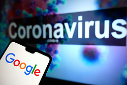 The Google logo seen displayed on a mobile phone with an illustrative model of the Coronavirus displayed on a monitor in the background. Photo credit should read: James Warwick/EMPICS Entertainment