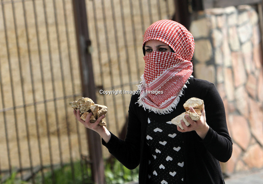 A female Palestinian protester throws stones at Israeli soldiers during clashes in the West Bank city of Bethlehem, February 25, 2013. Photo by Imago / i-Images...UK ONLY