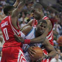 16 March 2009: New Orleans Hornets guard Chris Paul (3) attempts to drive between Houston Rockets defenders Aaron Brooks (0) and Dikembe Mutombo (55) during a NBA game between the New Orleans Hornets and the Houston Rockets at the New Orleans Arena in New Orleans, Louisiana.
