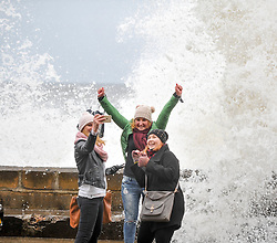 (c) Licenced to London News Pictures 21/03/2015. Scarborough, North Yorkshire, UK. (l-r) Malgorzata Zielinska, Karolina Zieconka and Agata Smith take a selfie with a wave. High tide brings huge waves to the shore at Scarborough. Photo credit : Harry Atkinson/LNP