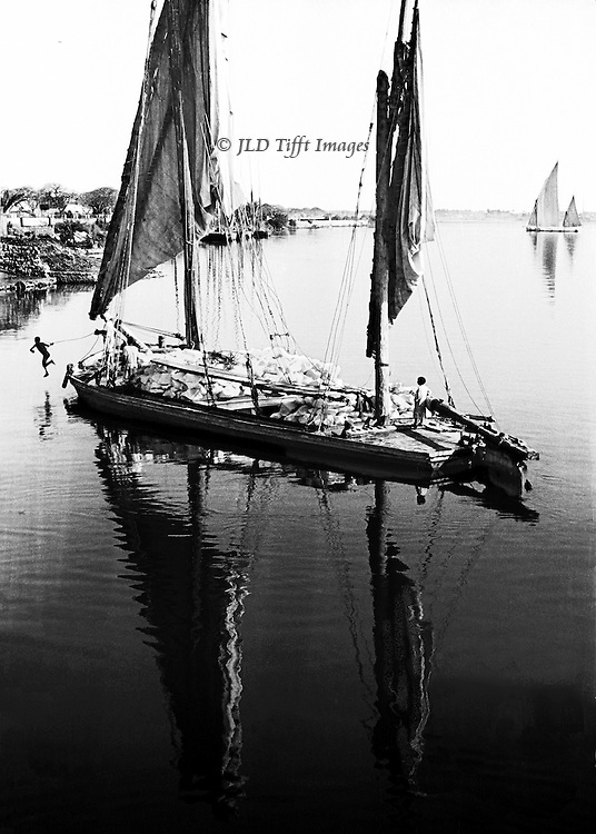 The two-masted sailboat, the traditional Egyptian felucca, is being used for freight -- a load of stone blocks (granite? marble?)  One crew member stands at the rudder while the other jumps off the bow into the water, holding the rope for tying it up.  Masts, sails, and jumper are all reflected in the still river water.