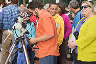 New Paltz, New York - A man looks through a filtered telescope as people gather on the State University of New Paltz campus to watch the Transit of Venus  on June 5, 2012. Venus crossed in front of the sun and was visible as a small black disk. The next Venus transit will not occur until 2117.
