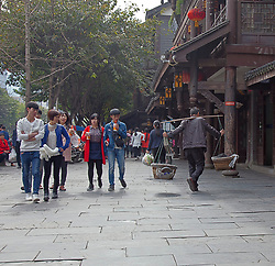 Today and yesterday:  A group of students pass a coolie with shoulder yoke, Chongqing, <br /> China.