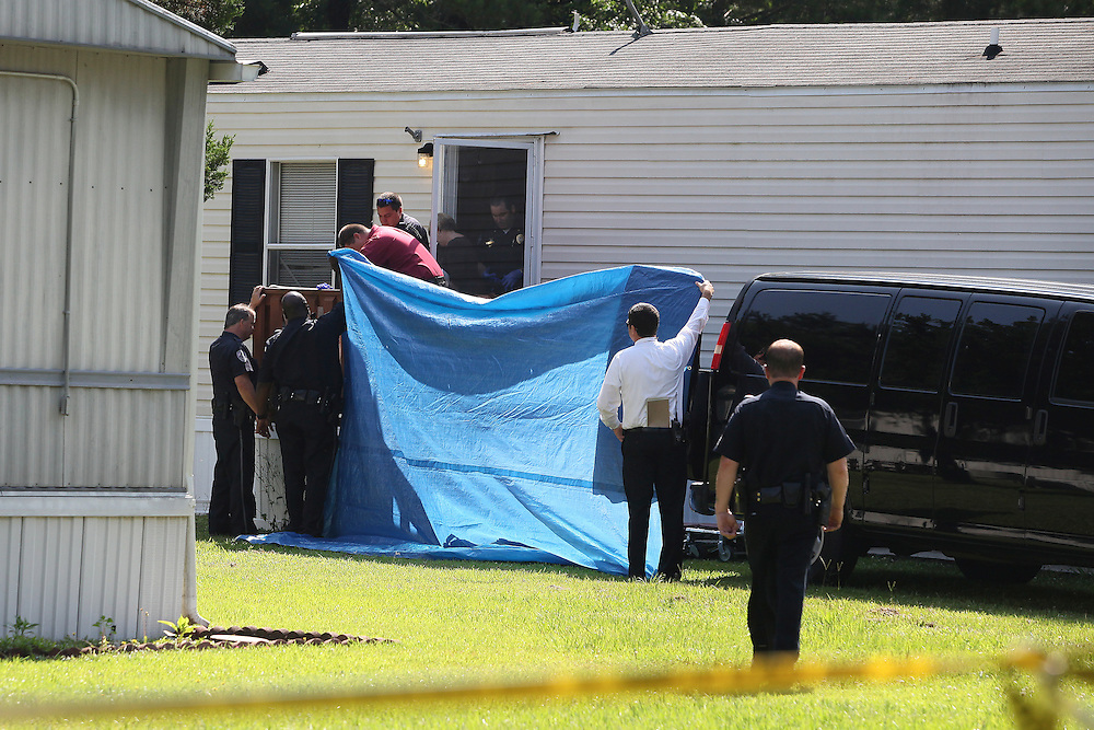 North Charleston police officers and Dorchester County coroner workers remove a body from a mobile home at 4674 Thoroughbred Drive, where authorities said a man fatally shot a woman during a domestic dispute, then turned the gun on himself Tuesday morning, June 18, 2013. (ANDREW KNAPP/STAFF)