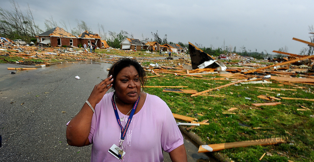 Daily Photo by Gary Cosby Jr...Homes in Camden Court area are completely destroyed following a large tornado, rated an EF5, that cut a path through Lawrence, Morgan and Limestone Counties, April 27, 2011.  Tamisha Cunningham suffered a leg injury when her home was destroyed. She looks over the damage while waiting for medical care.