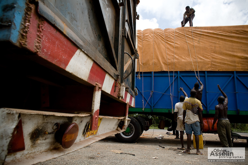 Men tie a tarp on the trailer of a large truck near Notse, Togo on Thursday October 2, 2008.