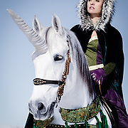 Conceptual fashion photographs taken by Janelle Pietrzak aka Explored Exposure of models Laura Pietrzak, Kendra Gross, and Courtnay Edwards, costumes by Zzyzx Couture, Makeup by Kendra Gross. Images depict three women in long velvet capes and renaissance costumes riding and handling two unicorns decorated with tassels walking in deep winter snow.